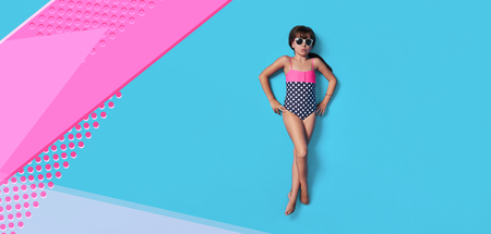 Fashion child summer. Little girl kid in swimsuit lay view top. Concept beach vacation. Blank, banner, copy space for ,advertising. Isolated pink, blue color background in studio.