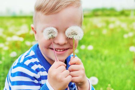 Happy face kid smile. Close up portrait joy child outdoors. Little boy playful smiling holding dandelions on eyes as eyeglasses. Joyful childhood, summer day. Background green grass. Foto de archivo