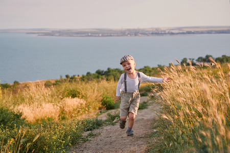 Happy child boy running on meadow in summer in nature. Little kid plays spring day on field. Beautiful smiling baby wearing fashionable retro about clothes, cap, suspenders.