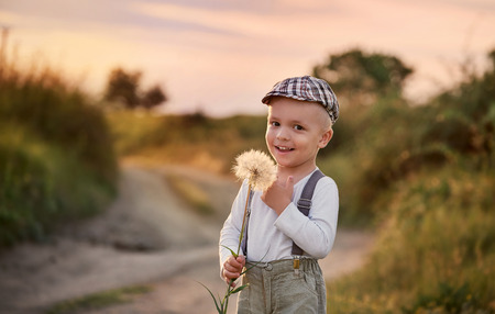 Happy child boy on nature spring,field,meadow,sunlight. Beautiful smiling baby holding big dandelion flower in his hands. Summer portrait little kid wearing fashionable retro clothes, cap,suspenders. Foto de archivo