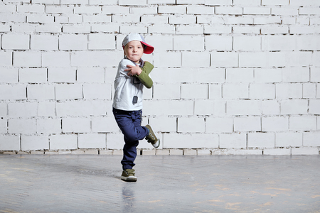 Child boy dancing. Cool kid hip hop break dancing on brick wall background. Little man movement, expressions in dance. wears a cap, sneakers, pants, t-shirt, street style.