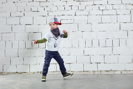 Cool child boy hip hop actively dancing to the music. Cute fashionable kid. Little rapper man wears a cap, sneakers, pants, t-shirt, street style clothes. studio, brick wall background. Foto de archivo