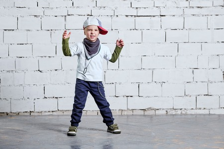 Cool kid boy dancing break dance.Hip-hop style. studio, brick wall background. Little rapper chiild man wears a cap, sneakers, pants, t-shirt, street style clothes.