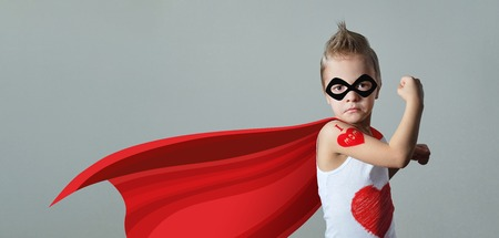 Funny strong child raising hand in success gesture. Little cool boy superhero loves mom, shows heart. Foto de archivo