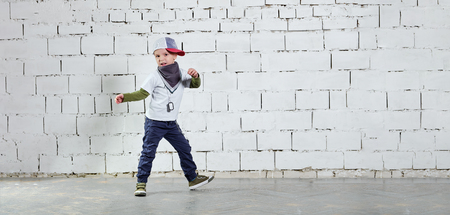 Child model posing in young rapper clothes. Cool kid boy dancing break dance.Hip-hop style. studio, brick wall background. Banner,copy space.