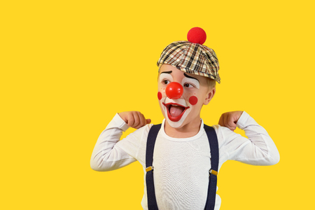Portrait funny child.Cheerful boy,costume clown,red nose,makeup.Emotional face little comic kid.Happy baby isolated yellow background.1 April fools day celebration. concept birthday, holiday, humor.