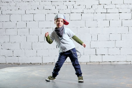 little child boy model posing in fashionable rapper clothes. studio, brick wall background. Cool young kid dancing break dance.Hip-hop style.
