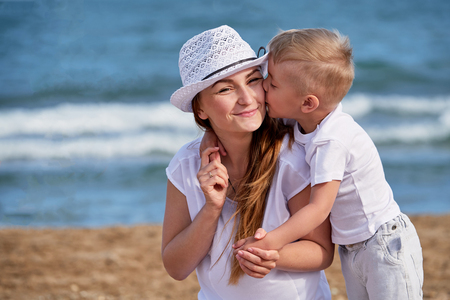 Happy family at sea summer. Little boy son hugs and kisses mother. Child loves mom. Portrait young woman in hat together with cute kid having rest on beach. concept of holiday, vacation. Foto de archivo
