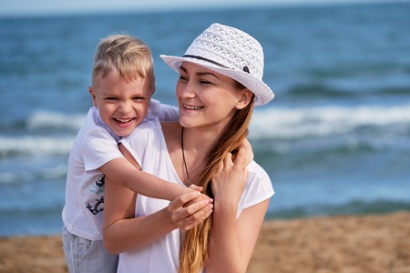 Happy little boy son hugs mother. Child loves mom,she looks away and smiles. Portrait young woman in hat together with cute blond kid having rest on beach. concept of holiday, vacation. Foto de archivo