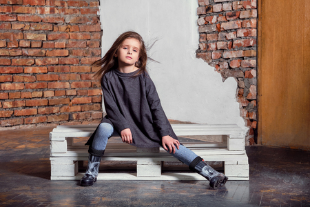 Little kid girl model posing fashionable in casual stylish clothes, gumboots. Fashion child sitting pose. studio background, brick wall.Shop youth, advertisement. Foto de archivo