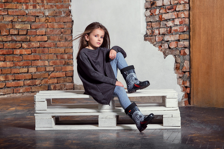 Fashion child posing sitting on pallets near brick wall. High fashion portrait of little girl. Attractive kid model in stylish, casual clothes, sweater, gumboots. Stock Photo