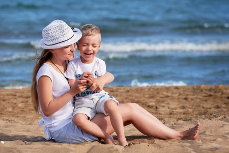 Young mother sitting on beach with son. Cute mom together child boy hugging, smiling, laugh, summer day. Happy childhood carefree playing on outdoor sand,sea, joy, fun. concept of holiday, vacation. Foto de archivo