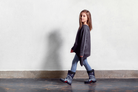 Fashion kid casual stylish clothes. Model child walks, pose. little girl poses near white wall, wears leggings, sweater, rubber boots. Full length portrait . Copy space.