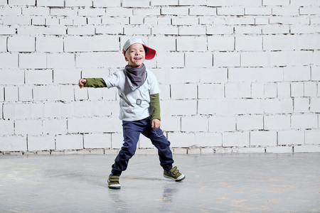 cheerful child boy dancing to music. Cool boy hip hop. Cute fashionable naughty kid.