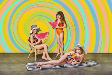 Summer fashion kids. Group little girl in swimsuits for sunbathing.