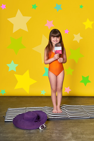 Fashion summer little girl, bright background,stars,studio. Charming child in swimsuit holding ice cream. 스톡 콘텐츠