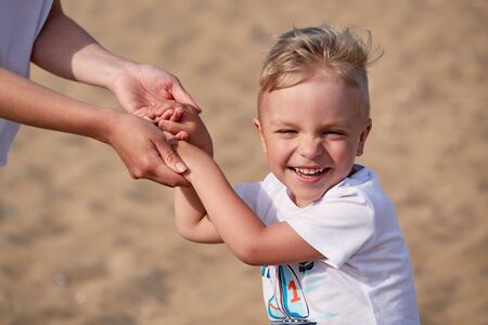 Portrait laughing child holding mother hands. Summer family day with parent. Attractive face little boy, background of sand beach. Caucasian kid smiling.