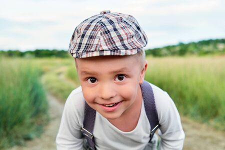 Funny happy child close-up. Attractive little boy looks into the camera with interest. Little kid smiling wears stylish cap, summer day. Pleased portrait.
