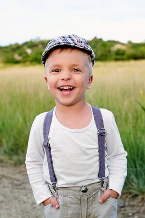 Funny happy child laughs, wears cap, suspenders, white t-shirt. Portrait kid boy in stylish retro clothes, outdoors. Summer spring day. Foto de archivo