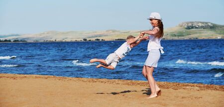 Young mother in summer clothes in hat together with son on beach. Carefree playing on outdoor sand,sea, joy, fun. Child boy, girl walking on coast. background panoramic,banner, copyspace. Foto de archivo