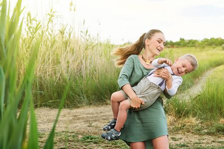 Happy parent loves her child. Mom and son carefree playing in nature outdoors,summer day. Little kid boy laughs and smiles with his mother. Concept family. background,light field grass.