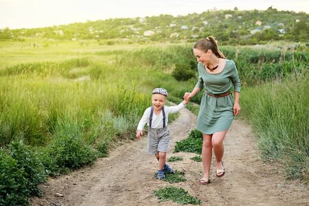 Mother and little son happy family. Attractive mom,kid boy are walking carefree outdoors summer.