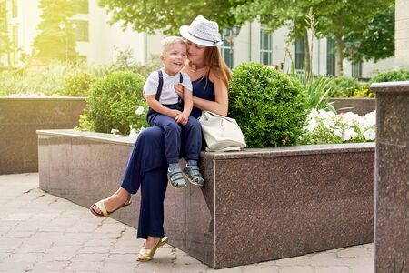 Mom holds a son in her lap. Young mother sitting in city park with little child boy. Happy kid smiles mom.