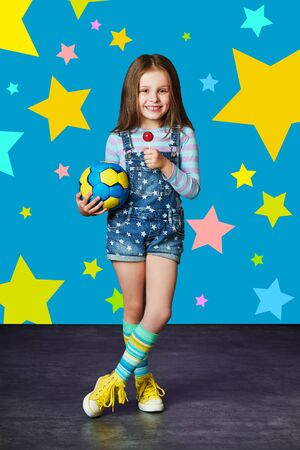 Cute little girl in denim against blue wall. Fashion concept.Child model in jeans overalls posing in studio, multi-colored stars background .