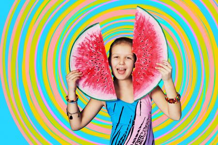 Funny summer portrait girl with watermelon. Child model in swimsuit posing in studio on colorful, rainbow background. Emotional, joyful face Caucasian kid.