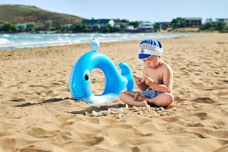 Little boy alone sits off coast. Child in hat playing with sand on beach sea. Holidays near ocean. Vacation, resort, lifestyle.