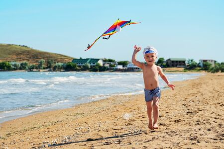 Boy playing on beach on summer holidays. Child running with flying a colorful kite in nature with beautiful sea, sand and blue sky. Happy kid on vacations, leisure.