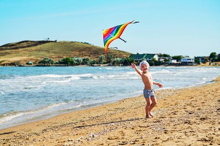 Happy laughing little boy flying a colorful kite in sand on beautiful beach. Child with beach toy. Kid play on ocean shore,sand and blue sky.