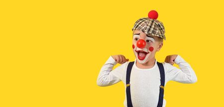 Portrait funny child clown.Cheerful boy,costume,red nose,makeup.Emotional face little comic kid.Happy baby isolated yellow background.