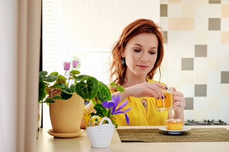 Girl sits at table with mug tea home. Pensive portrait young woman drinking hot drink. Cozy morning home. Foto de archivo