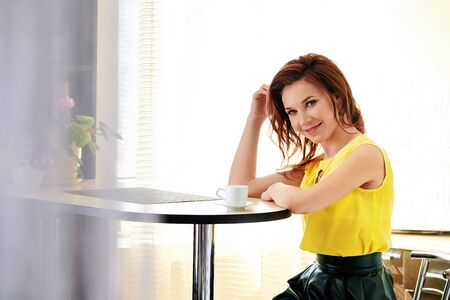Beautiful young woman with mug coffee sitting at table. Portrait attractive girl in bright room, sunshine background. Cozy summer day. Foto de archivo