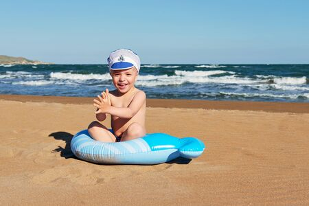 Happy baby sitting on the beach at leisure playing. little boy smiles while resting on a vacation, on a warm summer sunny day. Resort, lifestyle.