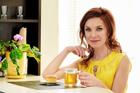 Beautiful young woman with mug tea sitting at table at home. portrait caucasian young woman in yellow blouse. Light background.