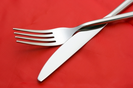 Fork and knife on red tablecloth photo