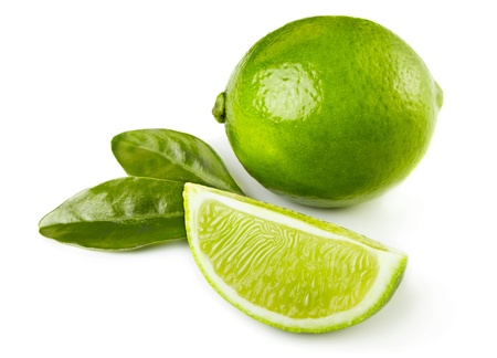 Whole and sliced limes with leaves isolated on white