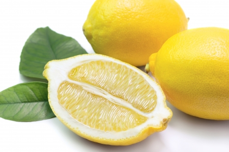 Lemons with green leaves isolated on white photo