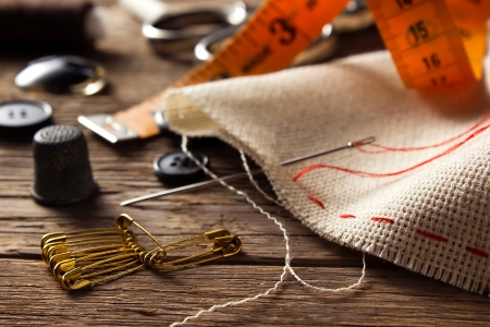 Sewing accessories on wooden background photo