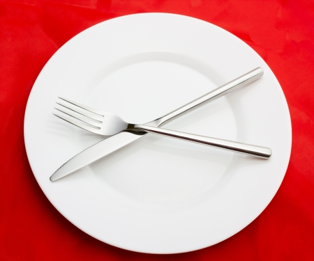 White empty plate with fork and knife on red photo