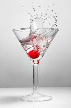 Splash of cherry in martini glass photo
