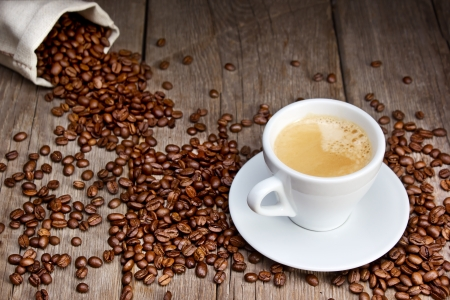 Coffee cup with beans on wooden background photo