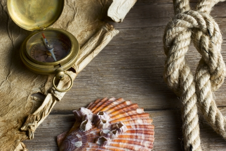 bygone: Old compass, rope and shell on wooden background