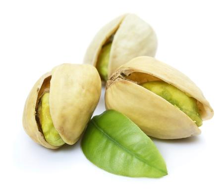 Tres pistachos con hojas aisladas en blanco