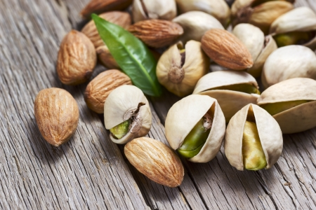 Almonds and pistachio with leaf on wooden background photo