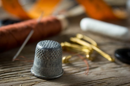 Dedal y de costura en el fondo de madera
