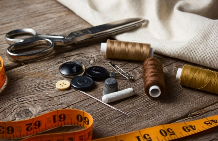 tailor: Sewing accessories: scissors, needle, thimble on wooden table