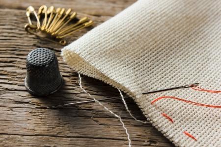 aguja, dedal y la textura de la lona de lino natural de la madera, tabla